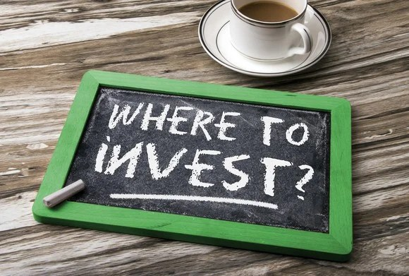 """Slate on table next to coffee cup with """"where to invest"""" written in chalk."""