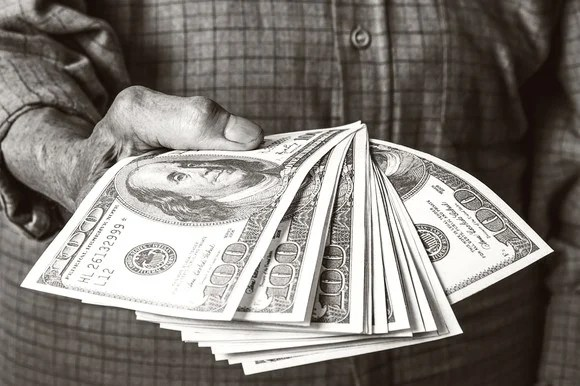 A man holding a pile of cash.