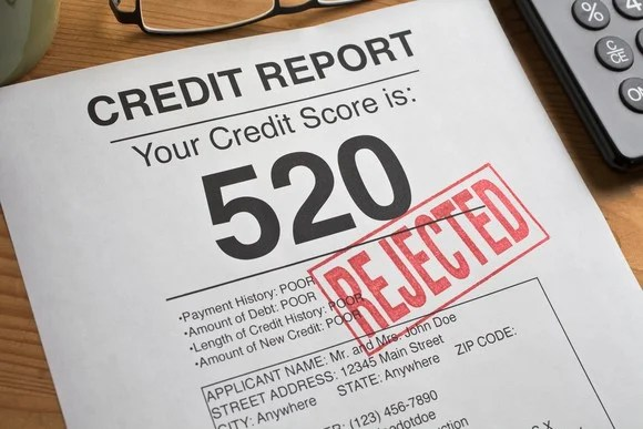 """Credit report with score of 520 and """"rejected"""" stamped on the page."""