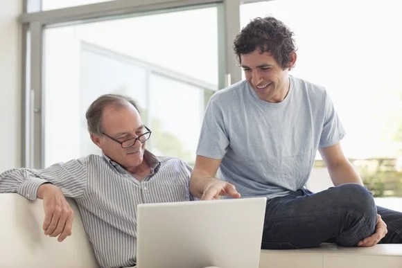 A father and son chatting in front of a laptop.