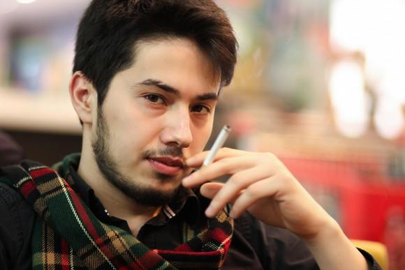 A young man smoking a cigarette.