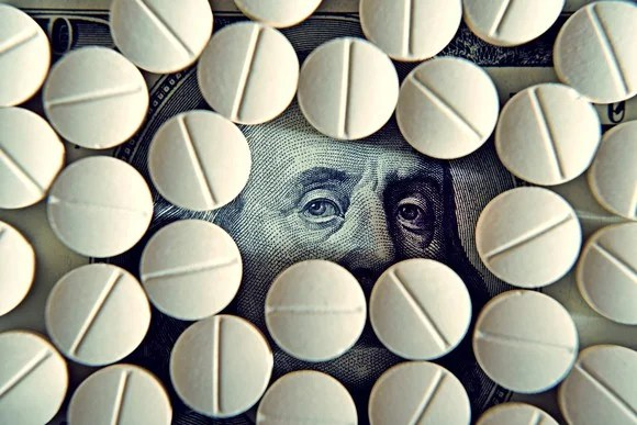 Prescription pills atop a hundred dollar bill, with only Ben Franklin's eyes being visible.