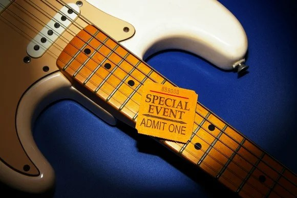 A simple event ticket, resting on the neck of a Fender Stratocaster guitar.