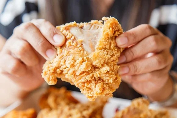 A man eating fried chicken.