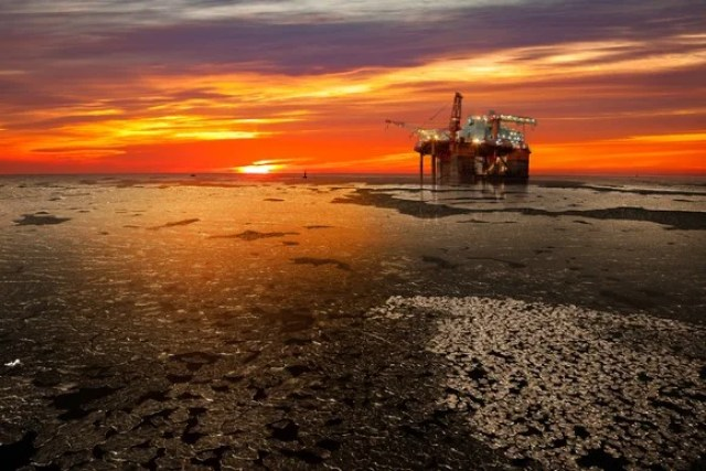 Offshore oil and rig platform in sunrise on frozen sea.