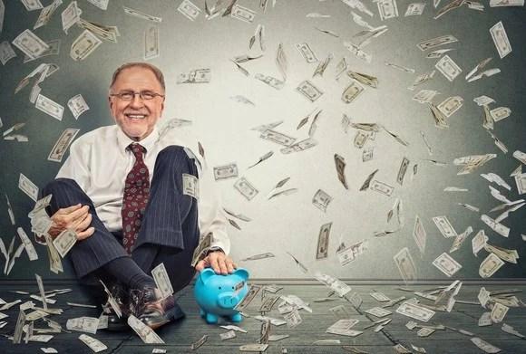 A man sitting on the floor next to a piggy bank as $1 bills fall from the sky.