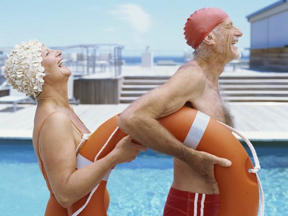 Two smiling seniors next to a pool.
