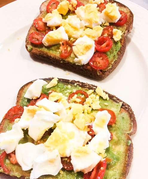 Two slices of avocado toast with boiled eggs and cherry tomatoes