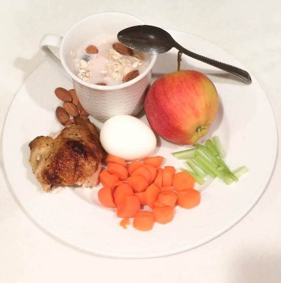 A plate with chicken, chopped carrots, celery sticks, apples, eggs, almonds, and a bowl of yogurt