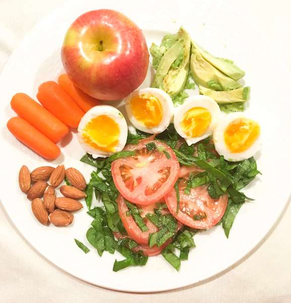 A dinner of salad, eggs, apples, carrots, almonds, and avocado