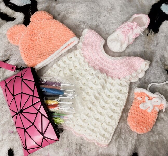 A knitted hat, dress, mitten, and shoe are on a bed