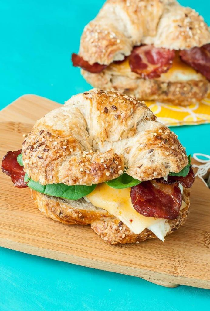 There are two croissant breakfast sandwiches with bacon, egg, cheese, and spinach in them.