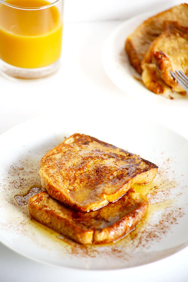 There is french toast bread with cinnamon sprinkled on top next to a glass of orange juice.