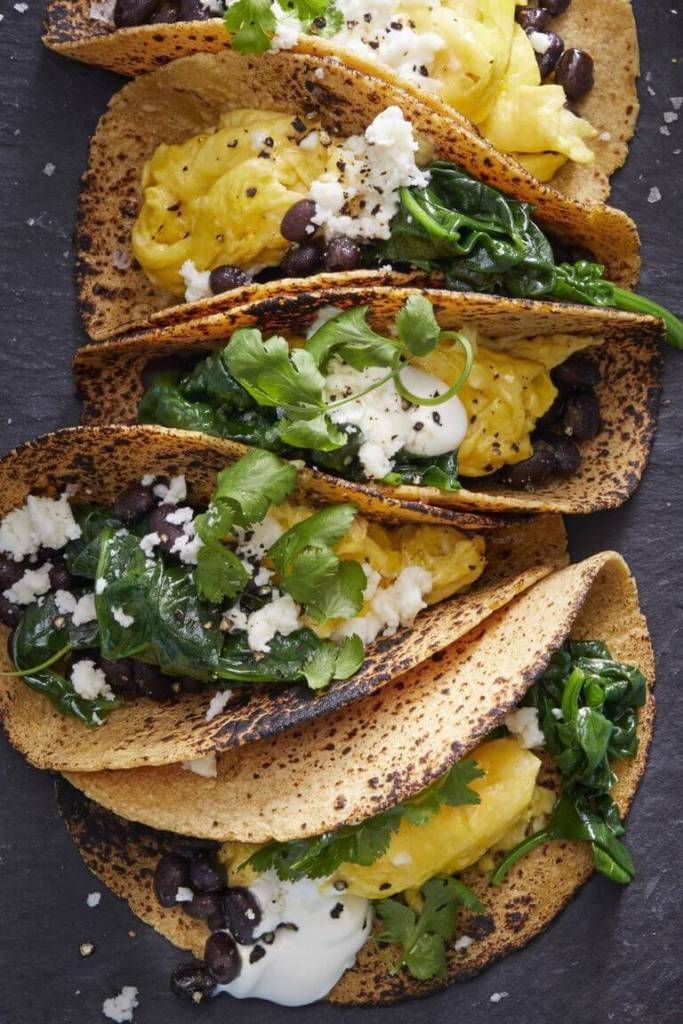 There are 5 tacos with scrambled eggs, green onions and cheese inside of them.