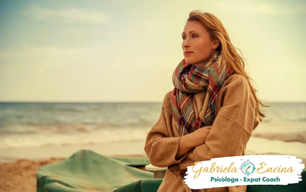 Soledad - Soledad intima - Mujer rubia con abrigo y bufanda mirando hacia el mar