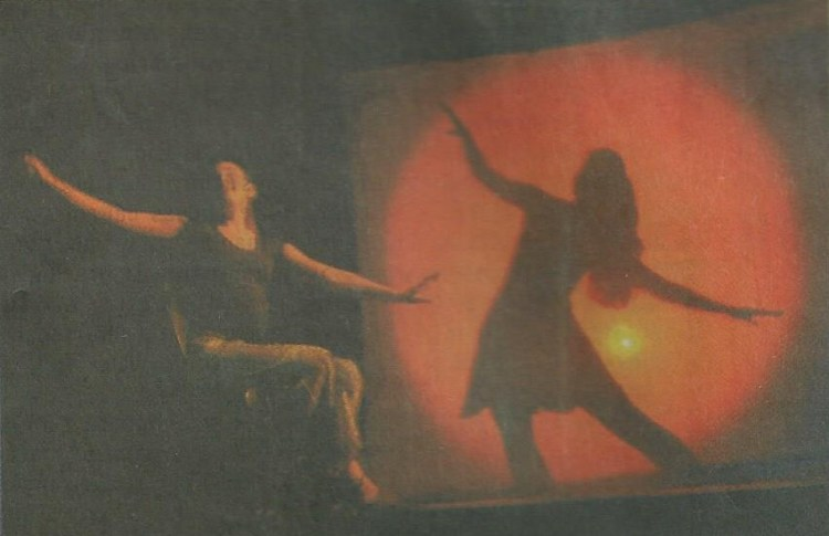 An actress on stage, pregnant, sitting on a chair. On the background, the shadow of a ballerina.