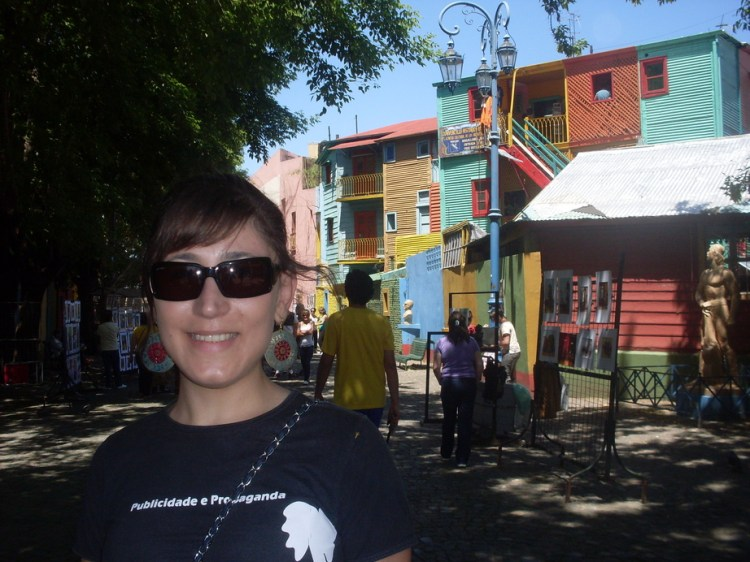 A young woman wearing sun glasses with colorful houses on the background.