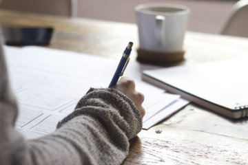 Hand holding a pen, writing on paper on a wooden table, notebook and cup on the background.