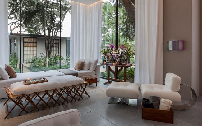 Projeto integra varanda, sala e biblioteca com decoração contemporânea e aconchegante