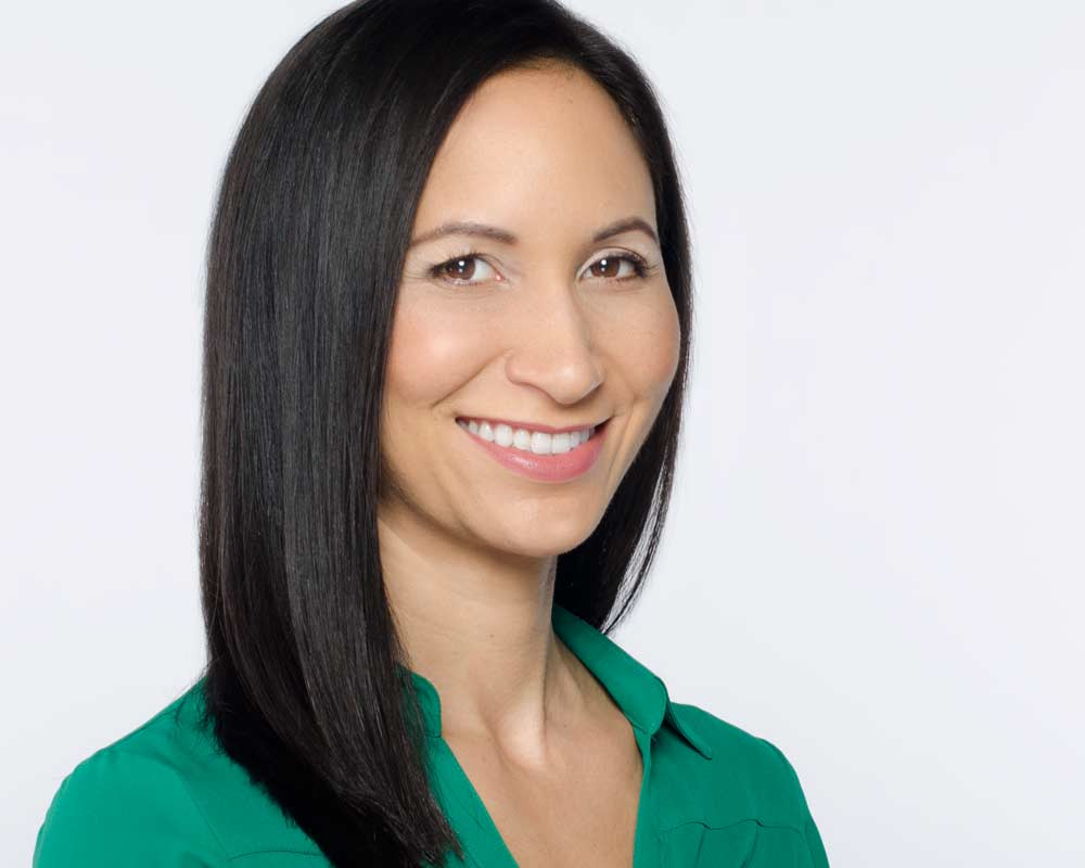 professional business corporate headshot of woman in green shirt against white background