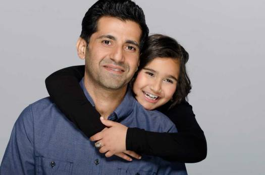 Studio family portrait of little girl hugging her dad