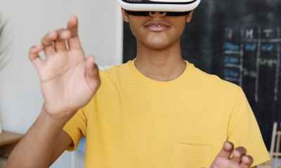 boy in yellow crew neck t shirt using white and black vr box