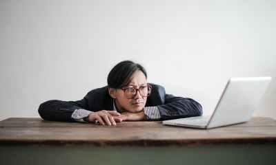 bored formal man watching laptop at desk