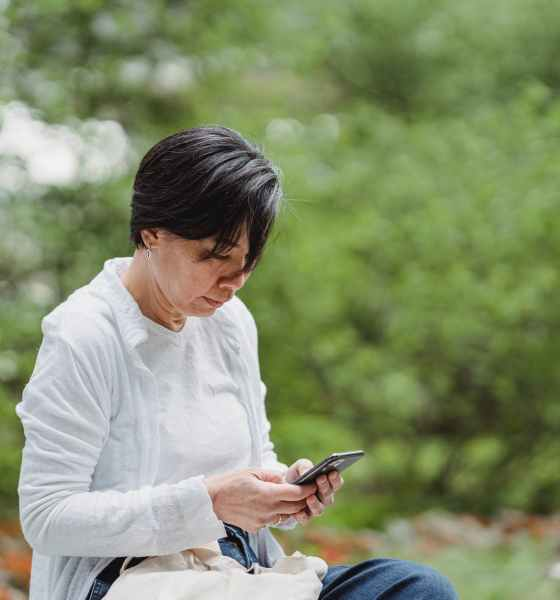 shallow focus photo of a woman using a smartphone