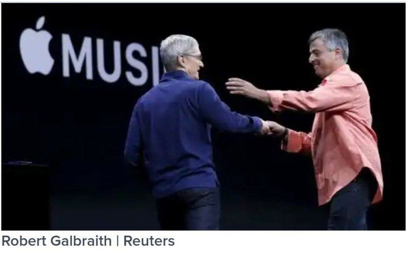 Apple CEO Tim Cook, left, greets senior vice president of internet services and software Eddy Cue