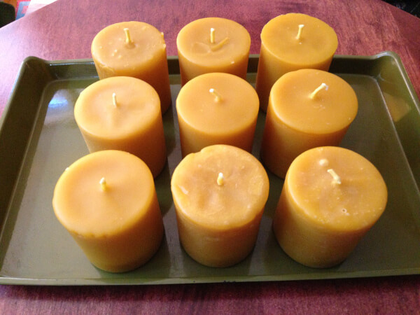 Nine unlit beeswax candles from the farmers' market