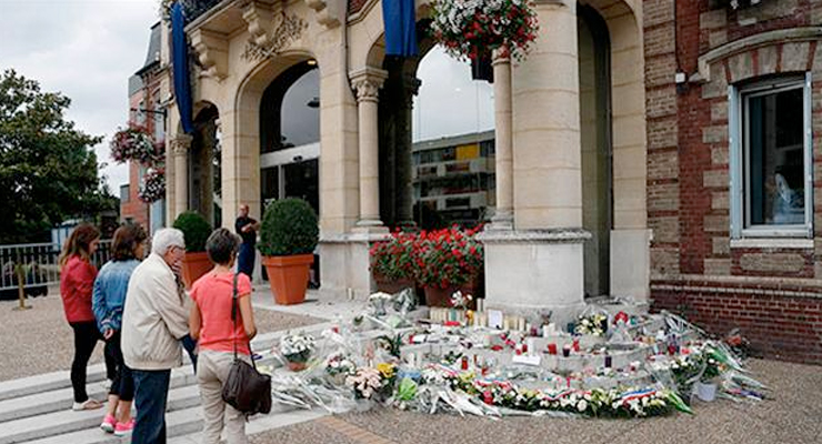 People gather to pay their respects at the makeshift memorial in front of the city hall after closed to the church where an hostage taking left a priest dead the day before in Saint-Etienne-du-Rouvray, Normandy, France, Wednesday, July 27, 2016. AP photo