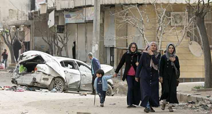 People walk near a damaged car in Syria's northwestern city of Afrin on March 22, 2018. (Reuters photo)