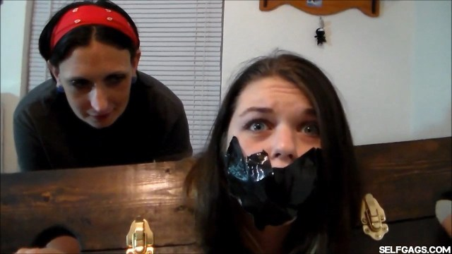Scared girl locked in stockade and tape gagged selfgags