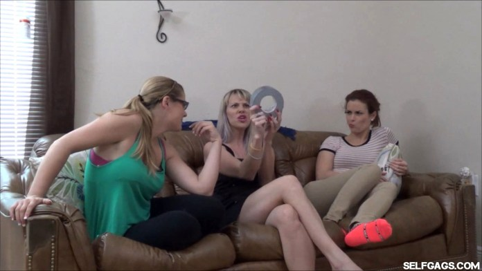 Vicky Vixxx shows Sunshine Tampa and Kendra Lynn a roll of duct tape at selfgags.com