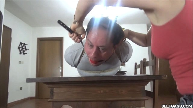 Hogtied man ball gagged by woman in femdom bondage