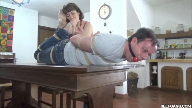 Woman worships hogtied man's feet