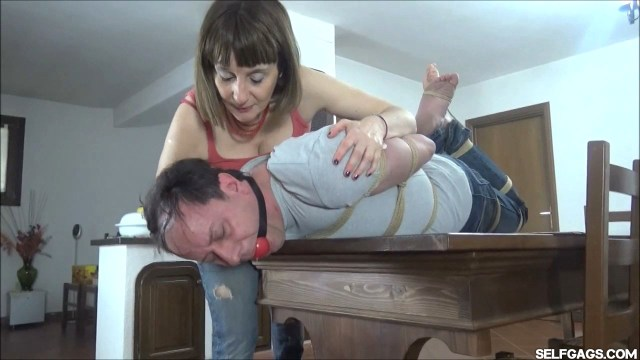 Woman has man hogtied and ball gagged in bondage