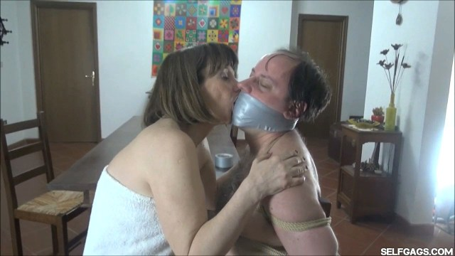 Woman kisses her bound and gagged male lover