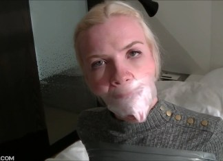 Blonde Vanessa with socks taped in her mouth under clear tape gag wrapped around her head