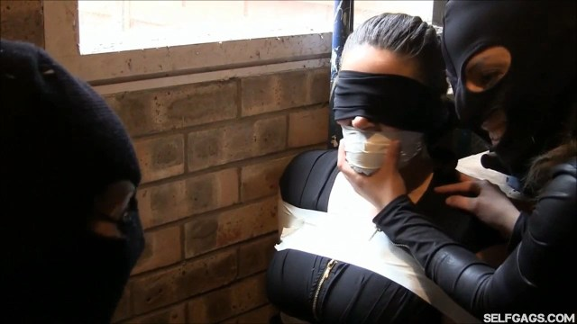 Tied up and gagged damsel is blindfolded by female catsuit burglars selfgags