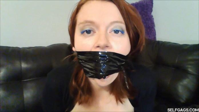 Redhead gagged with black bondage tape around the head