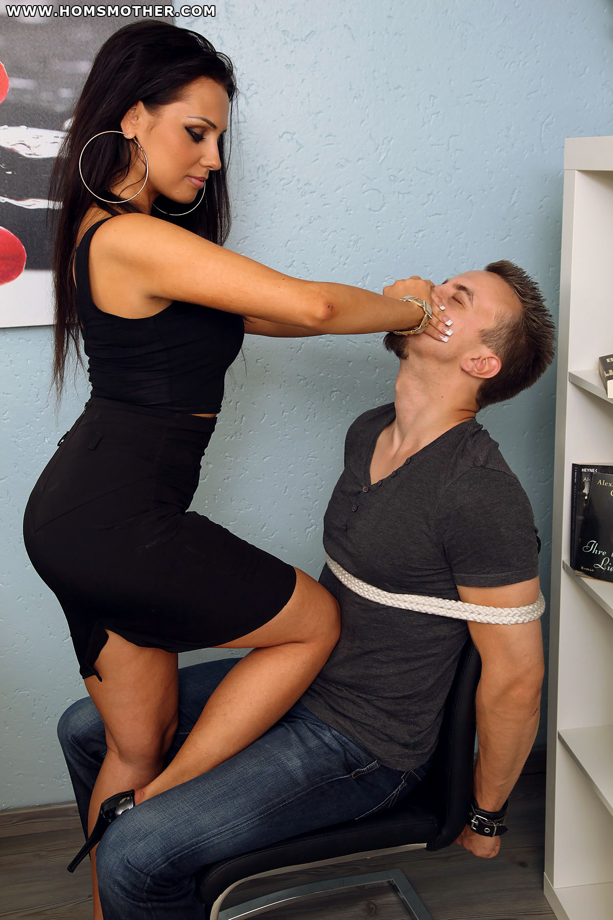 Sexy business woman with tied up male slave