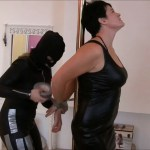 Black haired woman tied up with duct tape by female in leather catsuit