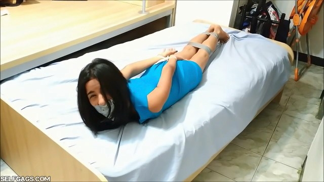 bound and gagged girl struggles on bed