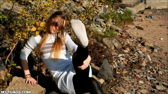 Sexy glamour model with sunglasses showing her feet and socks in the great outdoors
