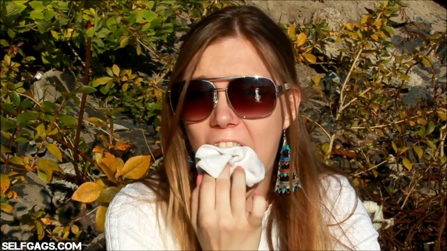 Girl with sunglasses stuffs dirty socks in her mouth