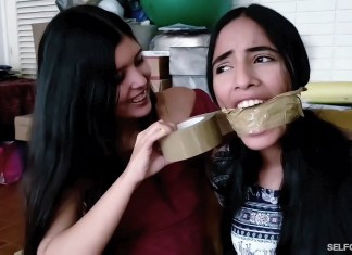 Sexy girl with dark hair gets tape wrap gagged by best friend in bondage