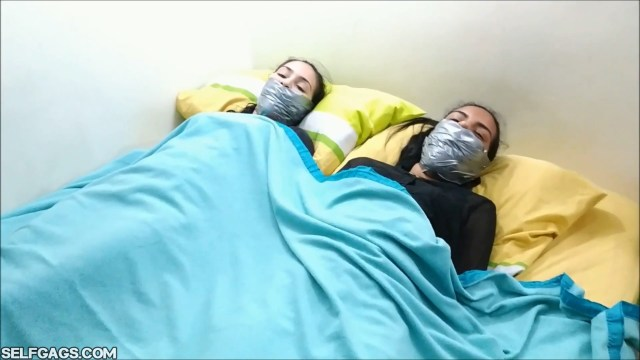 Two tied and tightly tape gagged latina sisters bound and gagged under a blanket in the bed