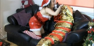 Mummified woman wrapped up in gift wrap paper by naughty elf
