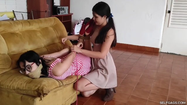 Bound and tape gagged girl hogtied in high heels on sofa